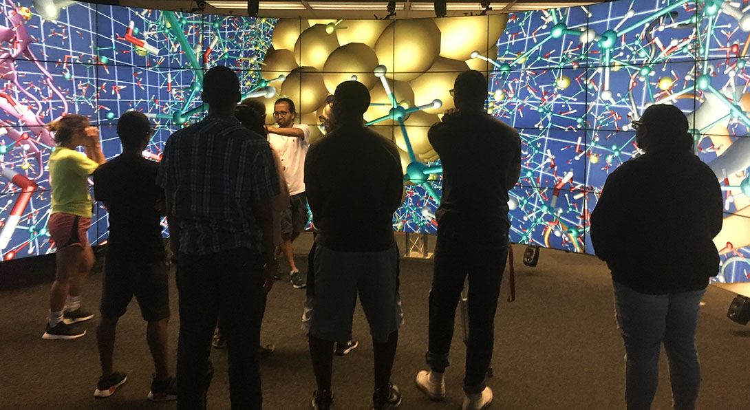 A small group of students stand listening to a presenter who stands in front of a wall of screens with colorful abstract graphics that look somewhat like molecules.
